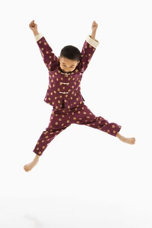 Asian boy in traditional attire jumping into air excitedly against white background. Stock Photo - 1868813