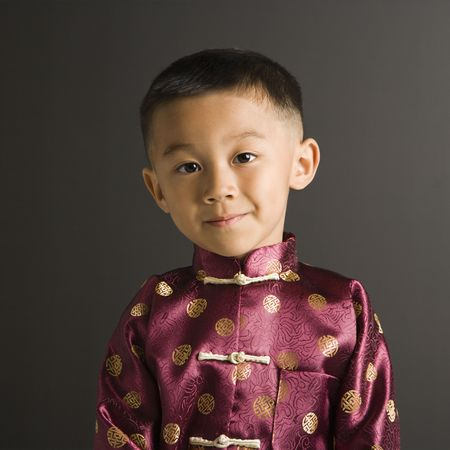 Asian boy in traditional attire standing against black background. Stock Photo - 1869039