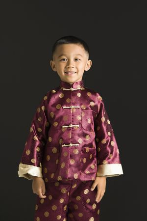 Asian boy in traditional attire standing against black background. Stock Photo - 1869025