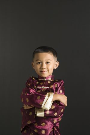 Asian boy in traditional attire standing against black background. Stock Photo - 1869031