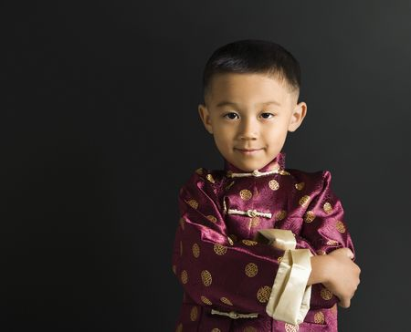 Asian boy in traditional attire standing against black background. Stock Photo - 1869001
