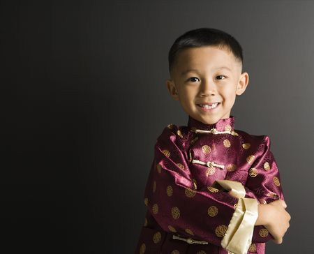 Asian boy in traditional attire standing against black background. Stock Photo - 1868979