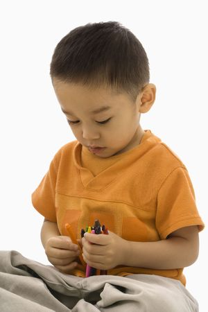 Asian boy sitting with handful of crayons. photo