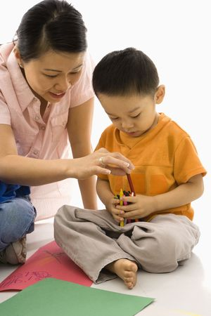 Asian boy and mother coloring with crayons. photo