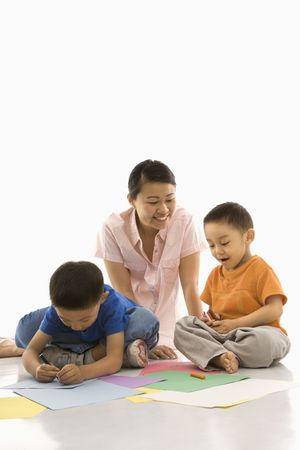 asian art: Asian mother with boys coloring. Stock Photo