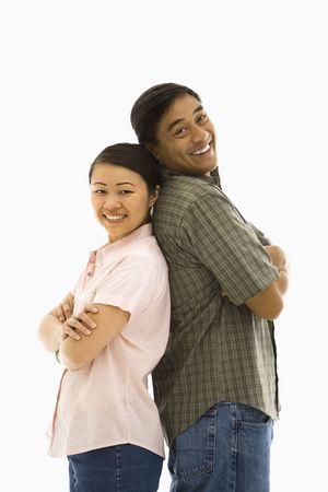 Asian man and woman standing back to back and smiling. photo