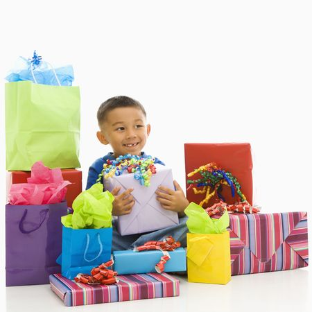 Asian boy sitting smiling with wrapped presents. photo