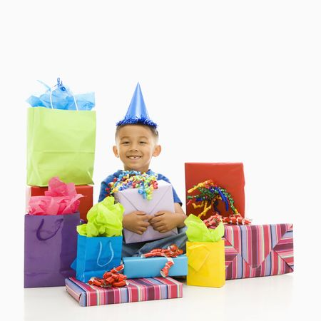 Asian boy sitting smiling wearing party hat with wrapped presents. photo