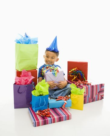 Asian boy wearing party hat sitting with pile of wrapped presents. Stock Photo - 1868938