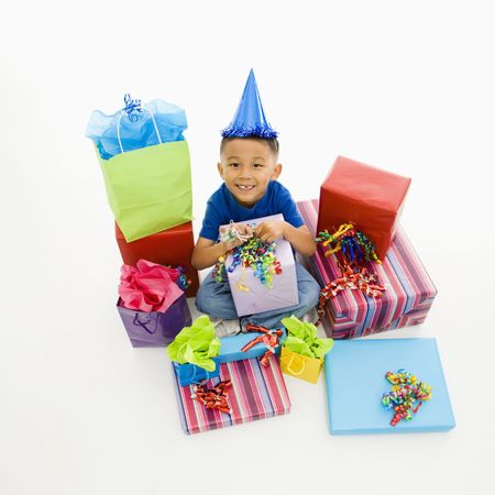 party hat: Asian boy wearing party hat sitting with pile of wrapped presents.