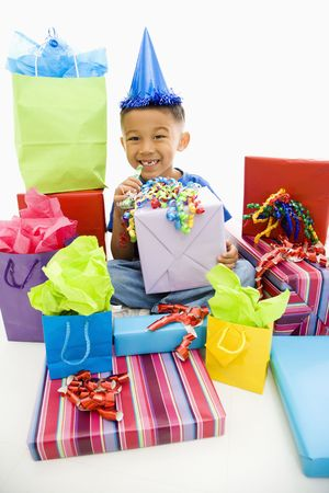 Asian boy wearing party hat sitting with pile of wrapped presents. photo