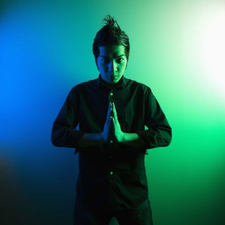 Portrait of attractive young Asian Filipino man standing holding hands in prayer position. Stock Photo - 1868993