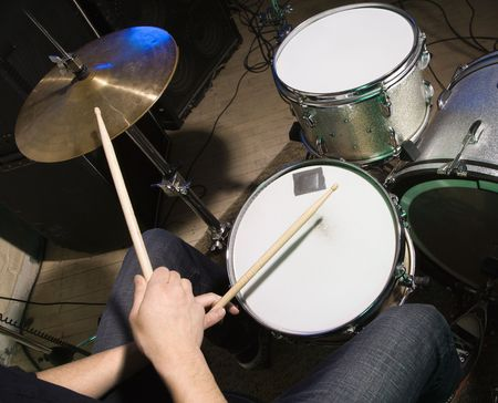 drumset: Above view of drummers hands holding drumsticks playing on drumset. Stock Photo