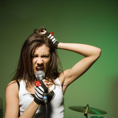 Caucasian female singing into microphone and pulling her hair. photo