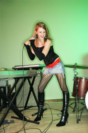 Caucasian female singing into microphone and laughing. photo