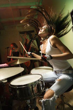 Kaukasische Mädchen-Band spielen Instrumente.