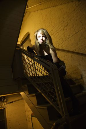 Caucasian female posing in stairwell with direct light on her face. photo