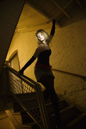 stairwell: Caucasian female posing in stairwell with direct light on her face.