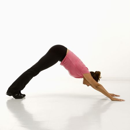 Side view of mid adult multiethnic woman wearing exercise clothing in downward dog yoga pose. photo