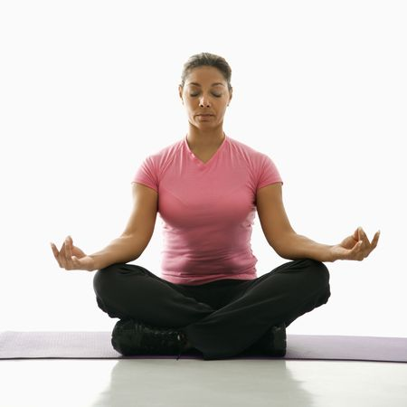 Mid adult multiethnic woman sitting in lotus position on exercise mat with eyes closed and legs crossed. Stock Photo