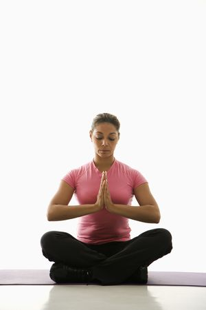 namaste: Mediados de adultos multi�tnica mujer sentada en posici�n Namaste en ejercicio tatami con los ojos cerrados y las manos en el centro.