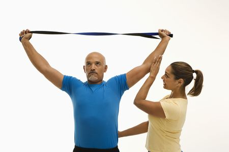 healthiness: Mid adult multiethnic woman assisting mid adult multiethnic man with stretching band.