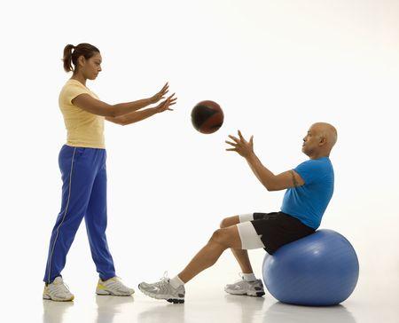mid adult man: Mediados de adultos multi�tnica mujer tirar pelota a mediados multi�tnica hombre adulto el equilibrio en azul excersise bal�n.