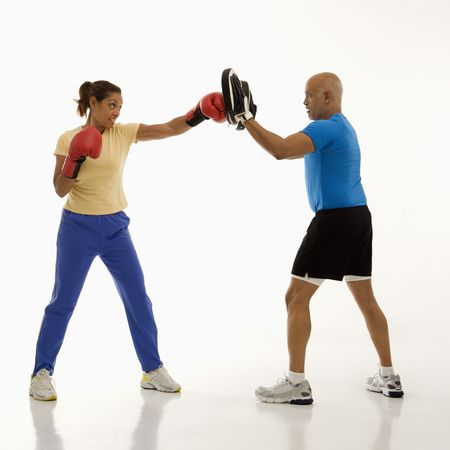 healthiness: Mid adult multiethnic woman standing and punching focus mitts worn by multiethnic mid adult man. Stock Photo