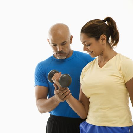 Mid adult multiethnic man assisting smiling mid adult multiethnic woman with dumbbells. photo