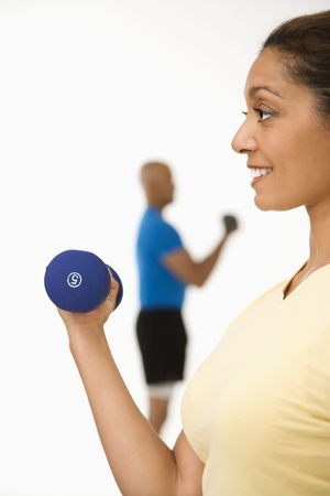 Close up of smiling mid adult multiethnic woman exercising using dumbbells with mid adult multiethnic man in background. photo