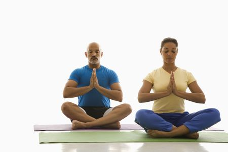 man meditating: Mid adult multiethnic man and woman sitting in Namaste position on exercise mats with eyes closed and hands at center. Stock Photo