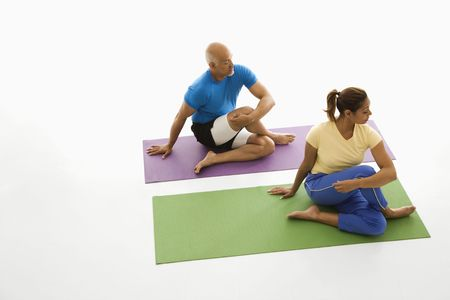 healthiness: Mid adult multiethnic man and woman sitting and stretching on exercise mats.