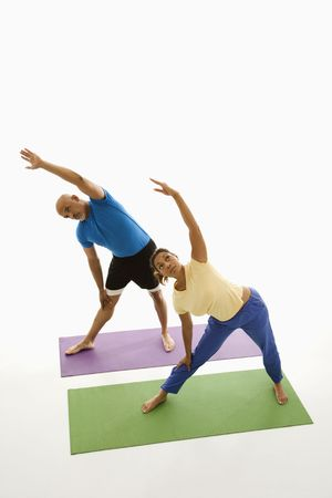 Mid adult multiethnic man and woman standing on exercise mats with arms extended overhead stretching. Stock Photo