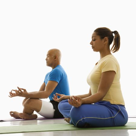 healthiness: Side view of mid adult multiethnic man and woman sitting in lotus position on exercise mats with eyes closed and legs crossed.