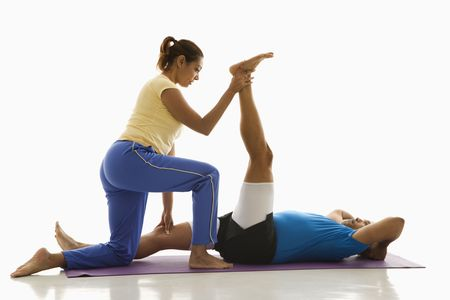 Side view of mid adult multiethnic woman assisting mid adult multiethnic man with stretching on exercise mat.