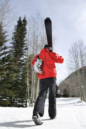 ski walking: Teenager walking and carrying ski gear. Stock Photo