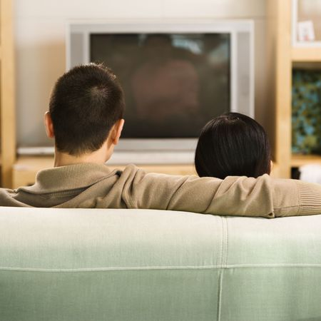 couple on couch: Asian couple sitting on couch watching TV.