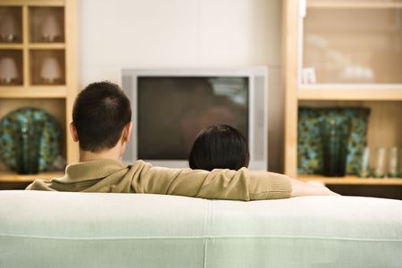 Asian couple sitting on couch watching TV. photo