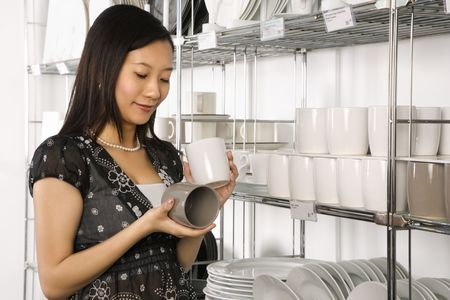 housewares: Asian female shopping for dishes and glasses in retail store. Stock Photo