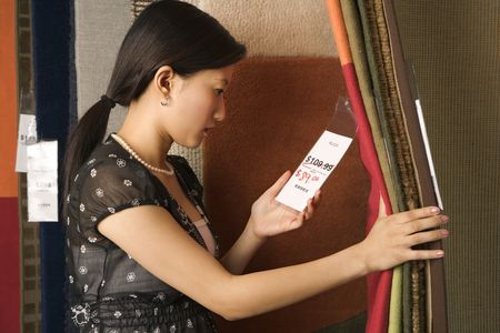 Asian female shopping rugs in retail store. Stock Photo - 1874742