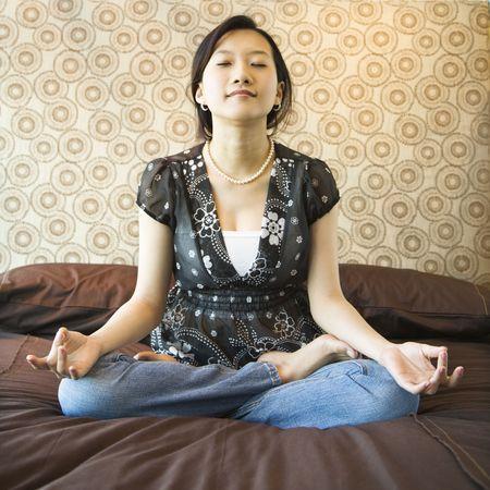 Asian female sitting on bed meditating. Stock Photo - 1874721