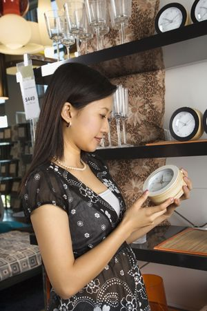 Asain female shopping for clocks in retail shopping setting. Stock Photo - 1874676