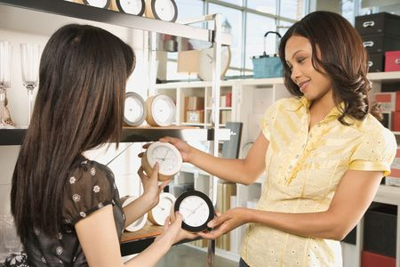 friends shopping: African-American and Asian women shopping for clocks in retail store.