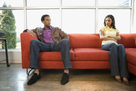 couches: African American couple sitting on couch in dispute.