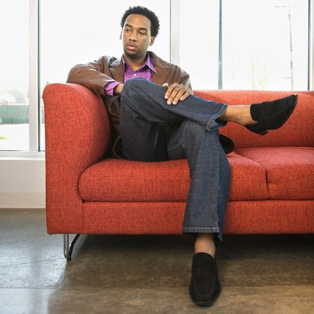 couches: African American male sitting on a red couch.