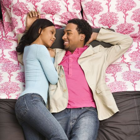 African American couple laying on bed looking at each other. photo