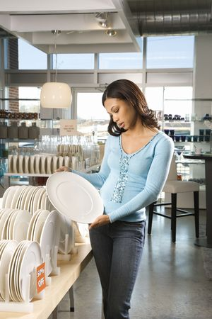 African American female shopping for plates in retail setting. photo