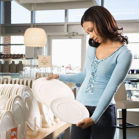 dinnerware: African American female shopping for plates in retail setting.