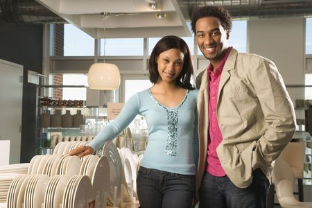 furnishings: Portrait of African American couple in home furnishings retail store.