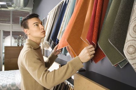 Asian male looking at fabric swatches in retail store. Stock Photo - 1874744